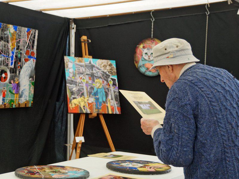 Un visiteur regarde une oeuvre au marché de l'Art de St-Germain-en-Laye